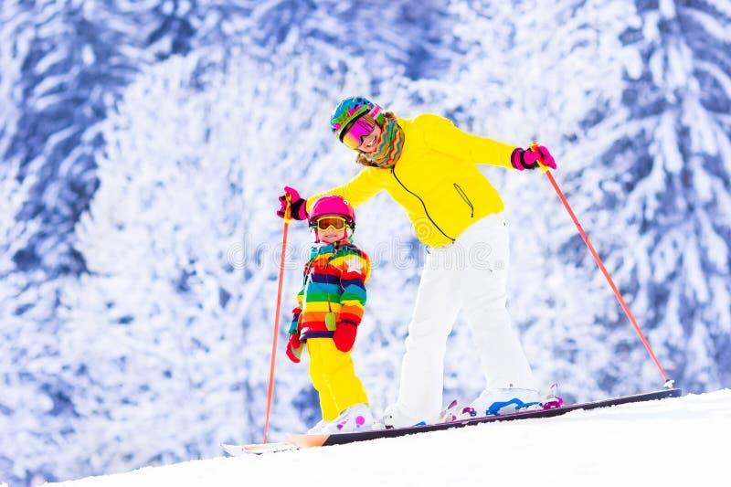 Mutter und kleines Mädchen, die lernen Ski zu fahren lizenzfreie stockbilder