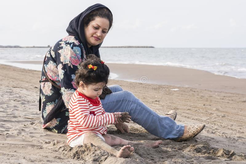 Mutter und Kleinkind mit Windel an Strand Sorgfalt und watchfulnes stockbild