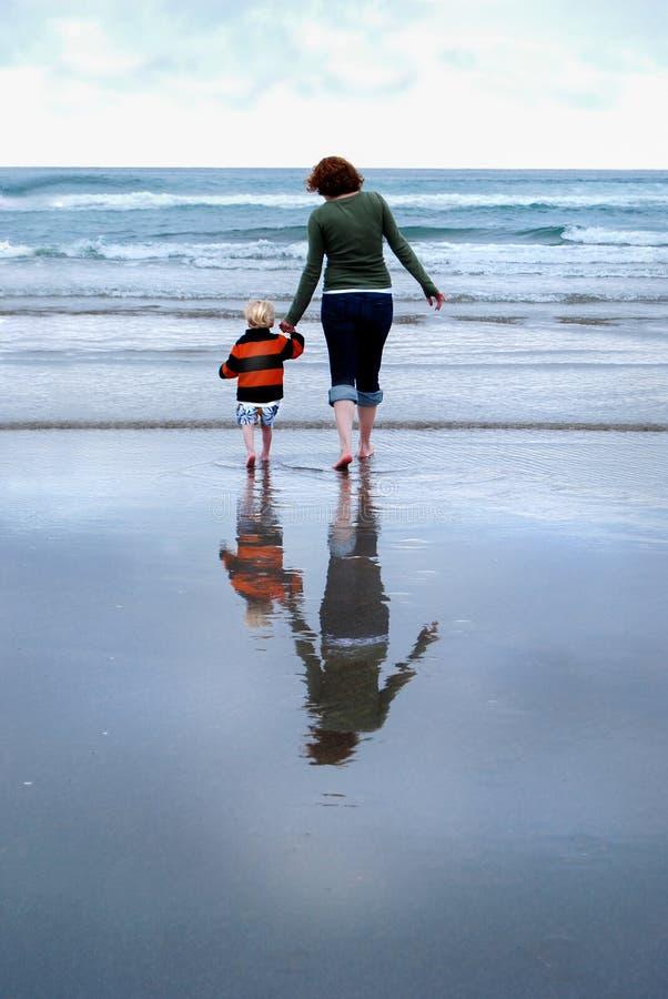 Mutter-und Kleinkind-Reflexion auf Strand-Vertikale lizenzfreie stockbilder