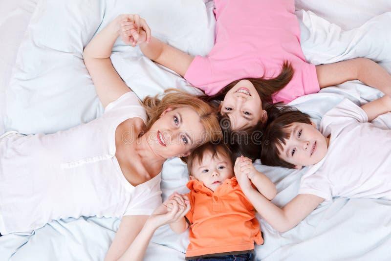 Mutter- und mit drei Kindernlügen stockfotografie