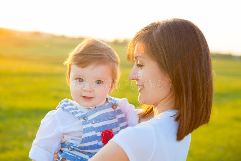 Mutter und reizender Sohn am sonnigen Feld mit Sonne glänzen lizenzfreie stockfotos