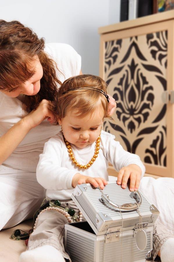 Mutter- und Schätzchentochter, die mit Schmuck spielt stockfoto