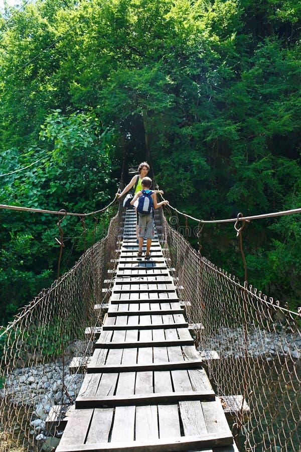 Mutter und seine Sohntouristen kreuzen den Gebirgsfluss auf Hängebrücke lizenzfreies stockbild