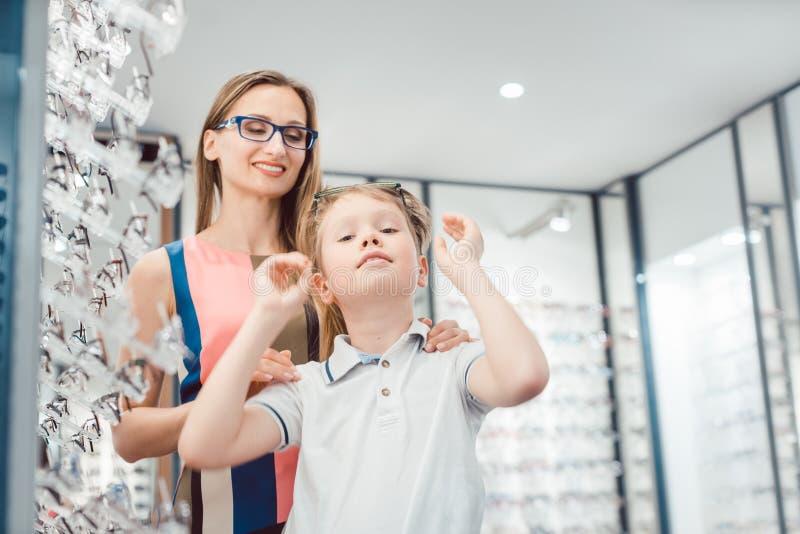 Mutter und Sohn beide, welche die Brillen angeboten im Optiker m?gen, kaufen stockbild