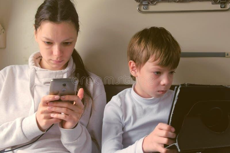 Mutter und Sohn in den Geräten, die mit dem Zug reisen, ist das Spielen Spiele in einem Wagen zweiter Klasse stockfotos