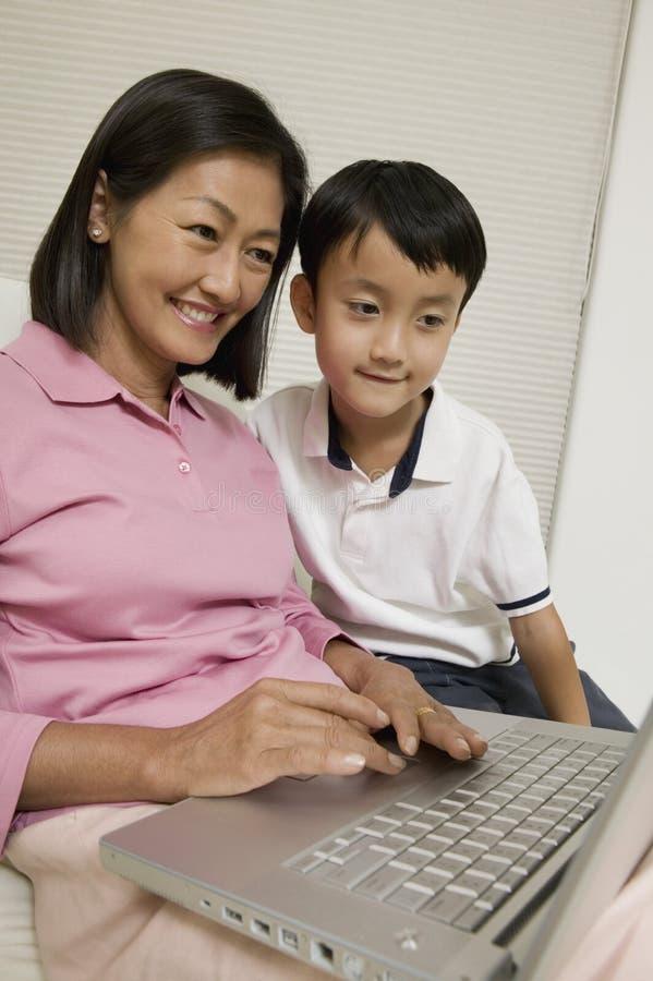 Mutter und Sohn, der Laptop im Wohnzimmer verwendet lizenzfreies stockbild
