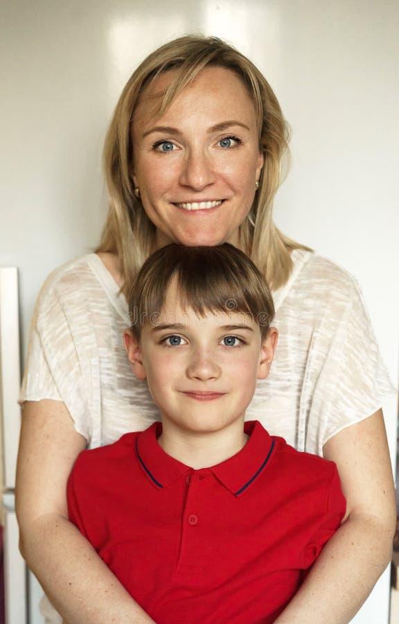 Mutter und Sohn des schulpflichtigen Alters Vertikales Portrait lizenzfreie stockfotos