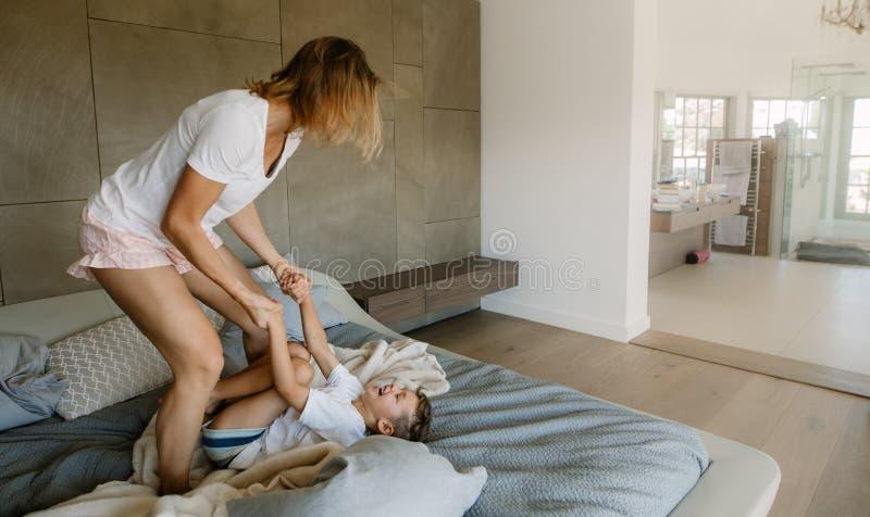 Mutter und Sohn, die auf Bett spielen stockbilder