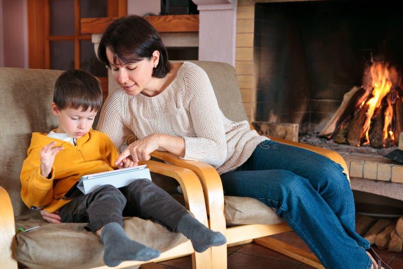 Mutter und Sohn, die auf digitalem Tablette PC spielen stockbild