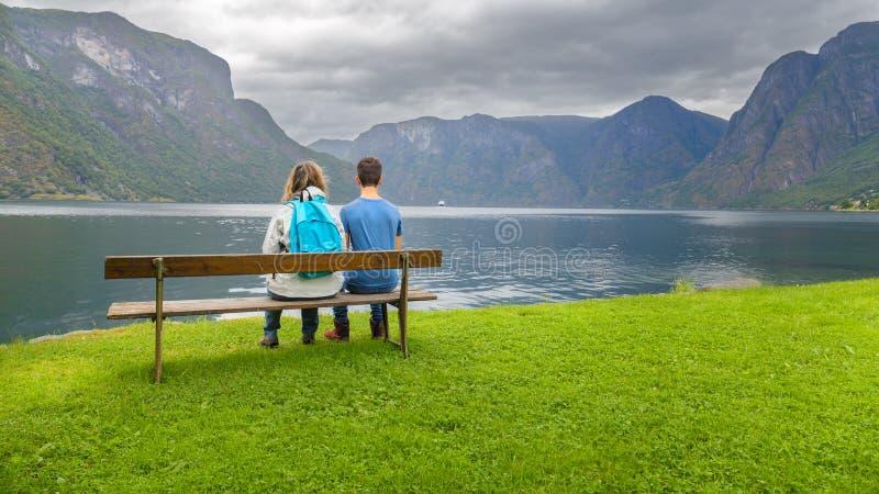Mutter und Sohn, die auf einer Bank betrachtet den Fjord sitzt stockbild