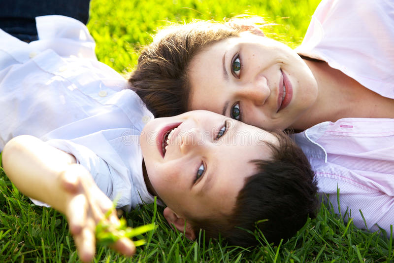 Mutter und Sohn, die auf Gras liegen stockfoto