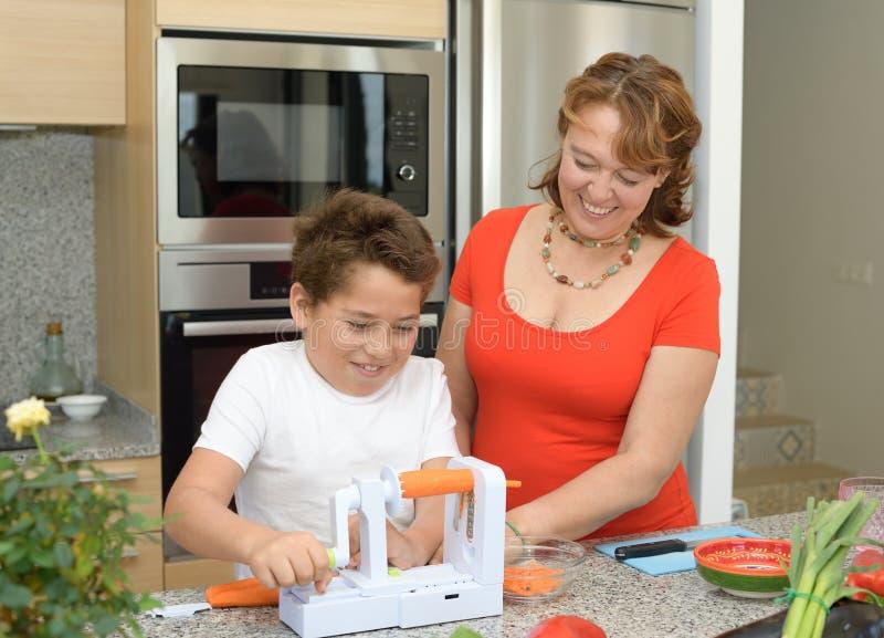 Mutter und Sohn, die das Mittagessen in der K?che vorbereiten Lachen mit einem Stück der Karotte lizenzfreies stockbild