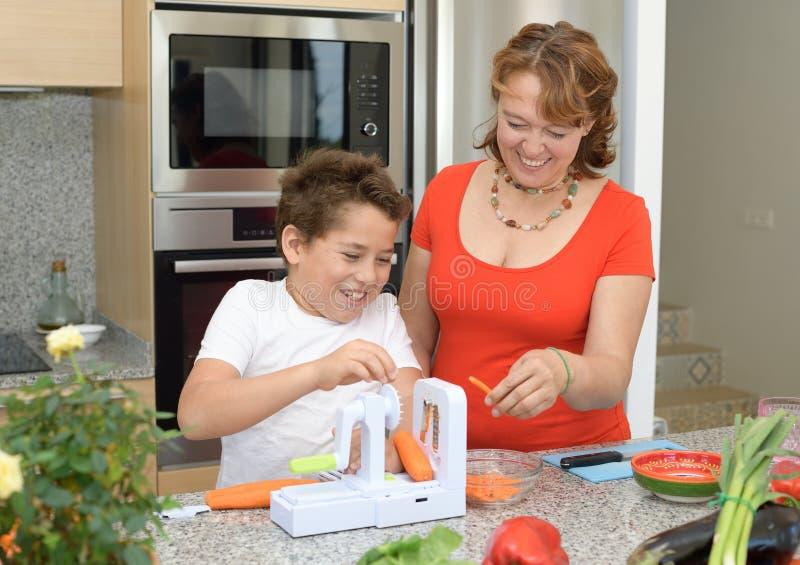 Mutter und Sohn, die das Mittagessen in der K?che vorbereiten Scherzen und Lachen mit einem Stück der Karotte stockfotografie