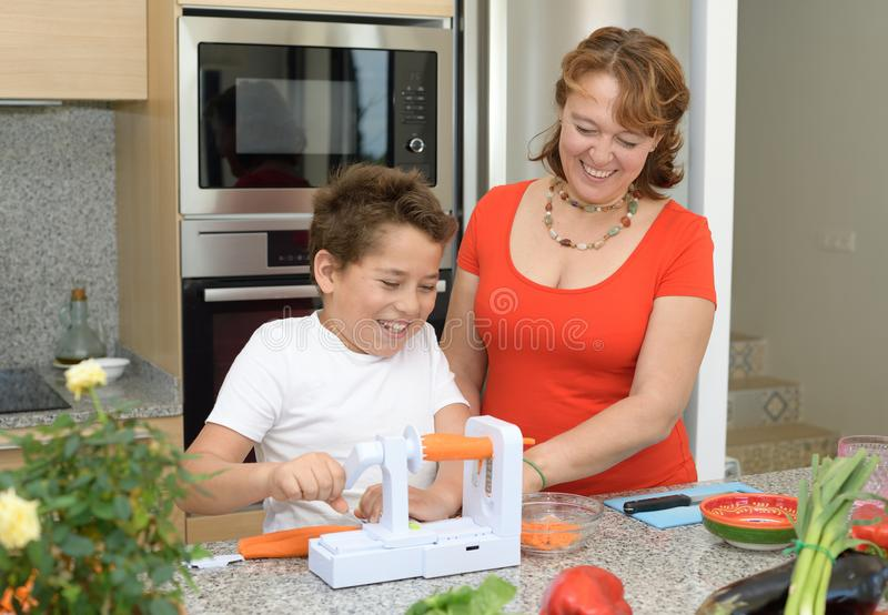 Mutter und Sohn, die das Mittagessen in der K?che vorbereiten Scherzen und Lachen mit einem Stück der Karotte lizenzfreies stockfoto