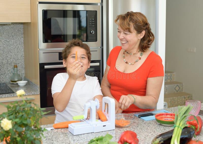 Mutter und Sohn, die das Mittagessen in der K?che vorbereiten Scherzen und Lachen mit einem Stück der Karotte stockfotos