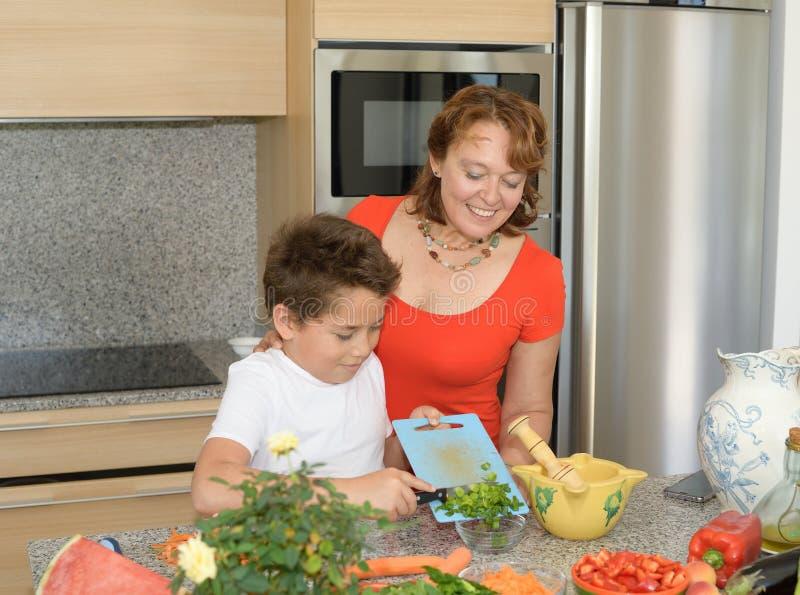 Mutter und Sohn, die das Mittagessen und Lächeln vorbereiten Kind setzt Knoblauch in eine Schüssel ein lizenzfreie stockfotografie