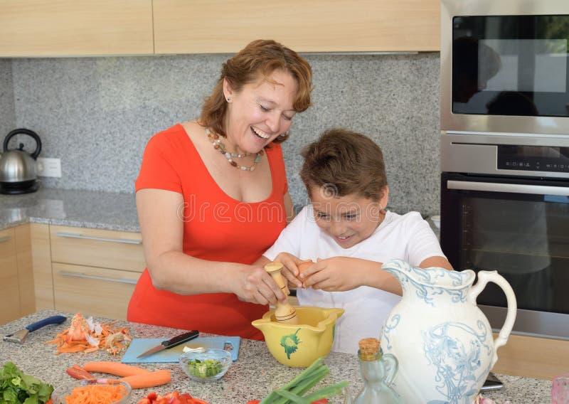 Mutter und Sohn, die das Mittagessen unter Verwendung der Eier und des Lachens vorbereiten lizenzfreies stockfoto