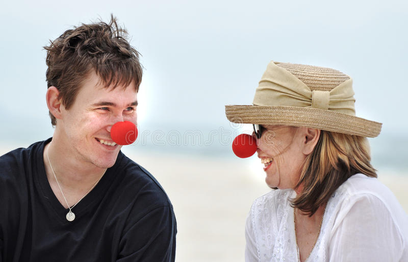 Mutter und Sohn, die den Spaß lacht hat, roten Nasentag auf schönem Strandurlaub feiernd stockfotos