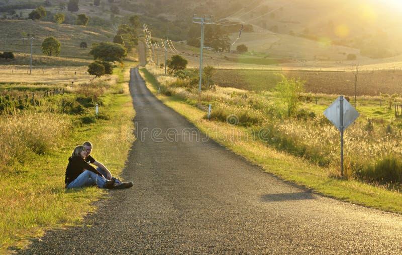 Mutter und Sohn, die durch lange leere aufpassende Sonnenunterganglandschaft der Landstraße sitzen lizenzfreies stockfoto