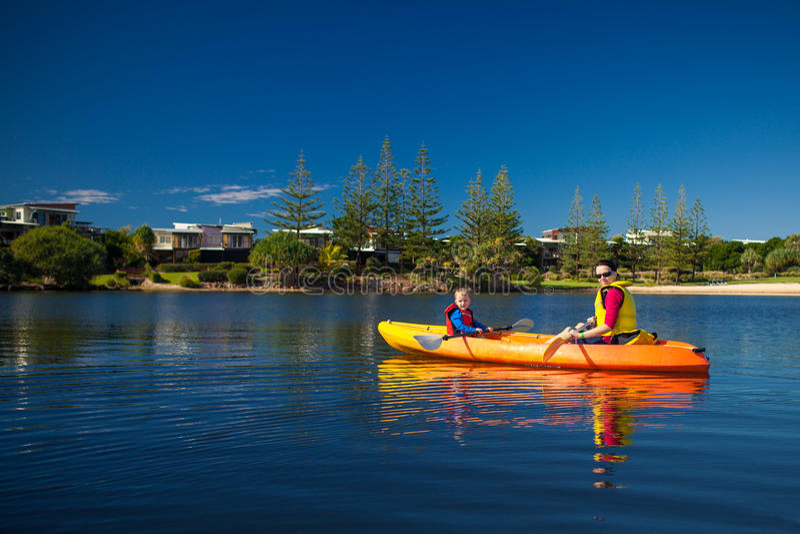 Mutter und Sohn, die in einem kleinen See Kayak fahren lizenzfreies stockbild