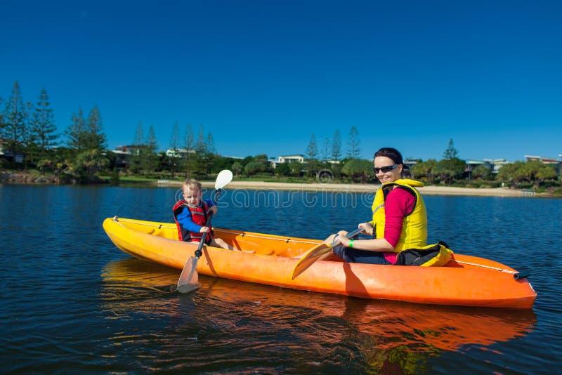 Mutter und Sohn, die in einem kleinen See Kayak fahren lizenzfreie stockfotografie
