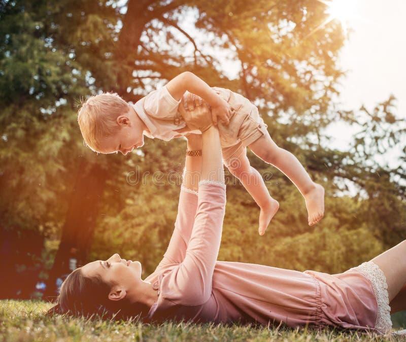 Mutter und Sohn, die einen großen Spaß im Park haben stockbilder