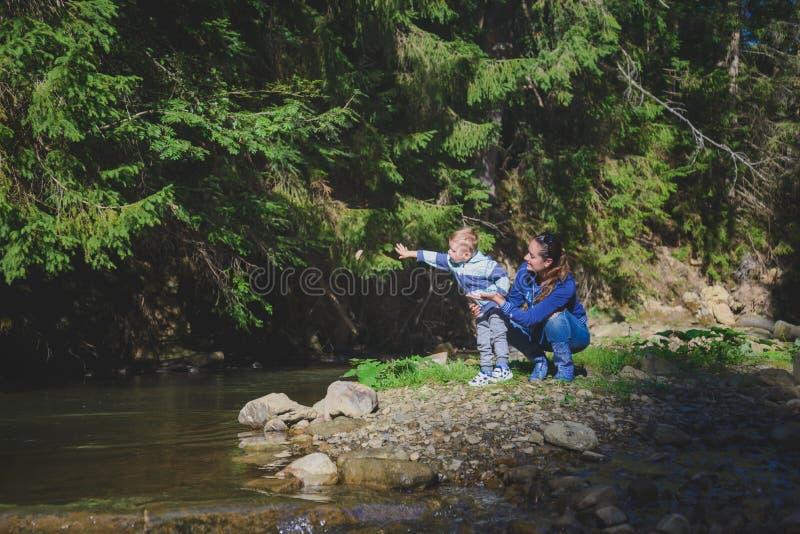 Mutter und Sohn, die im Fluss spielen stockfotos