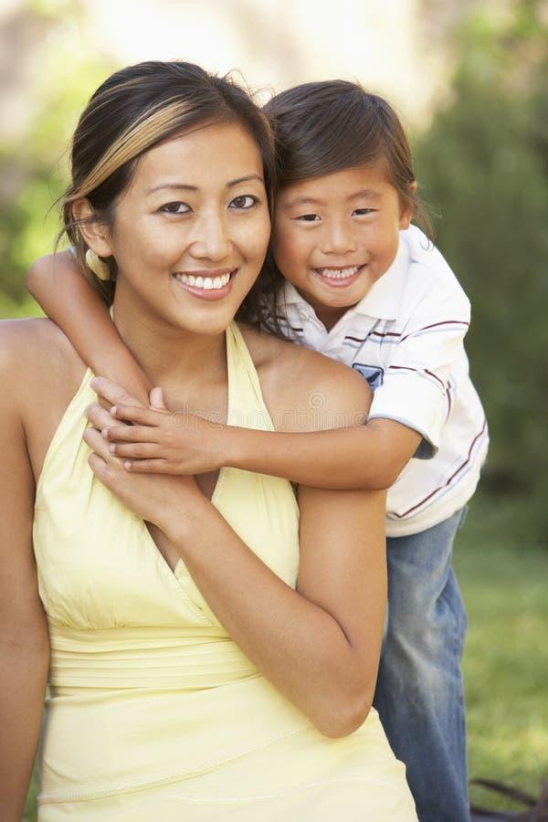 Mutter und Sohn, die im Garten umarmen lizenzfreie stockbilder