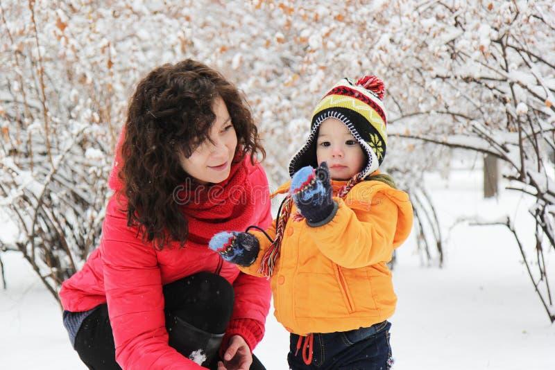 Mutter und Sohn, die im Winterpark spielen stockfoto