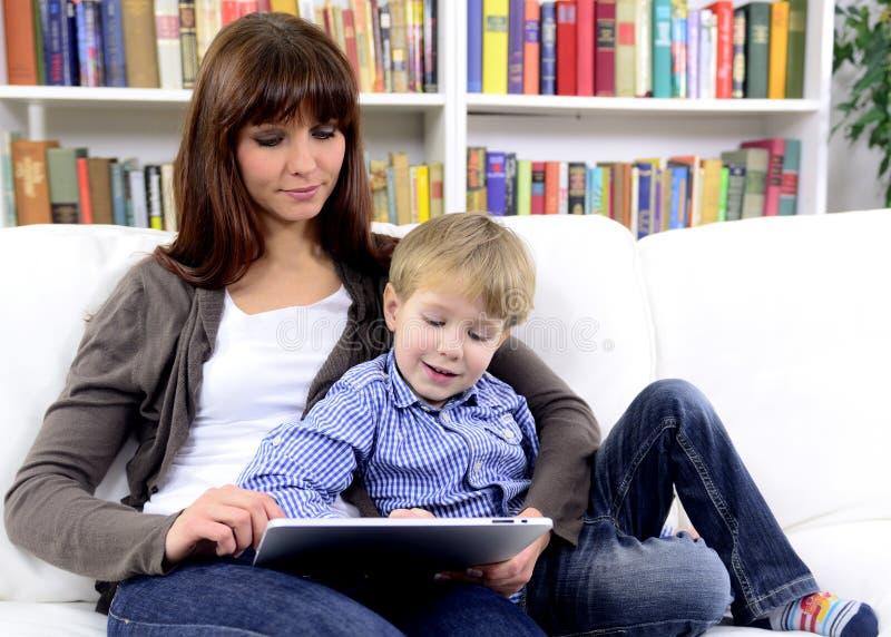 Mutter und Sohn, die mit digitaler Berührungsfläche spielen stockfotografie