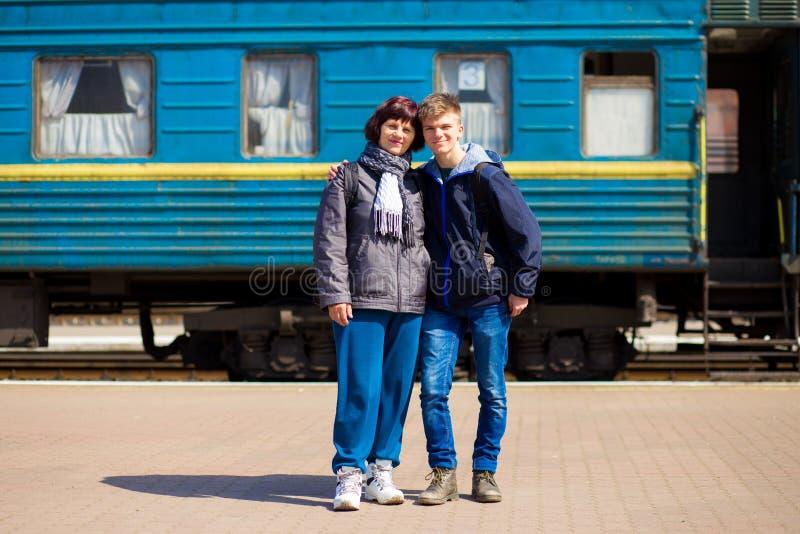 Mutter und Sohn, die nach langer Trennung am Bahnhof umarmen lizenzfreie stockfotos