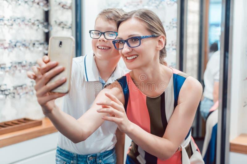 Mutter und Sohn, die selfie mit neuen Gläsern am Optometrikershop nehmen stockfoto