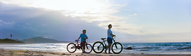 Mutter und Sohn, die am Strand radfahren stockfotografie