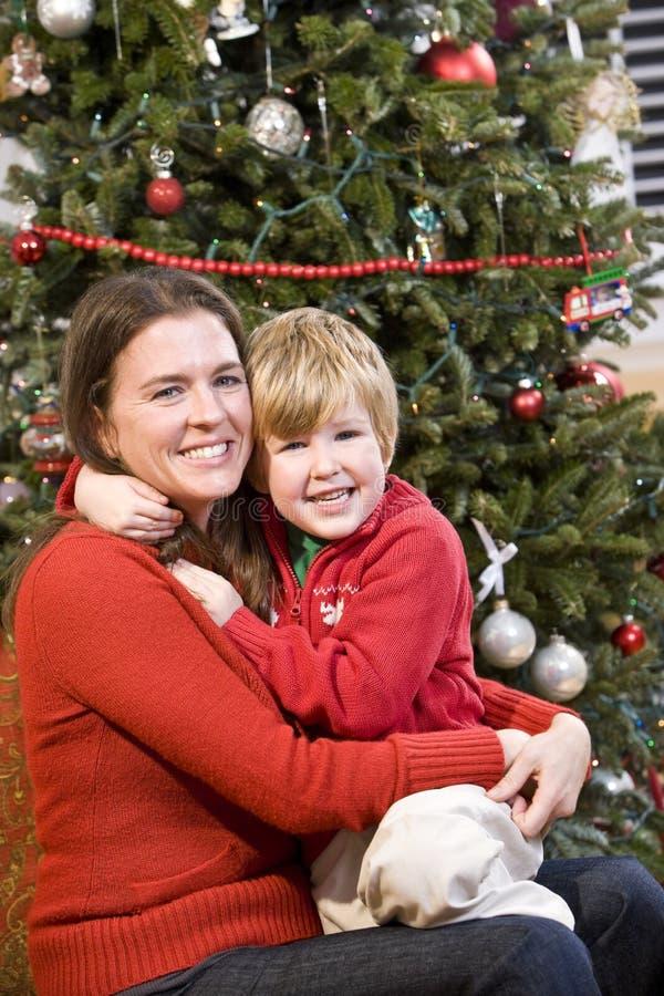 Mutter und Sohn, die vor Weihnachtsbaum umarmen stockfoto