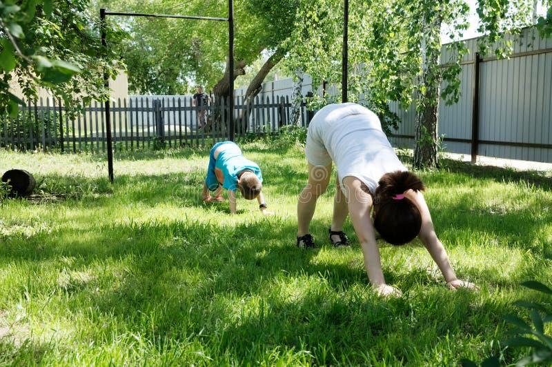 Mutter und Sohn, die Yogaübungen auf Gras im Yard zur Tageszeit tun Leute, die Spaß draußen haben stockfoto