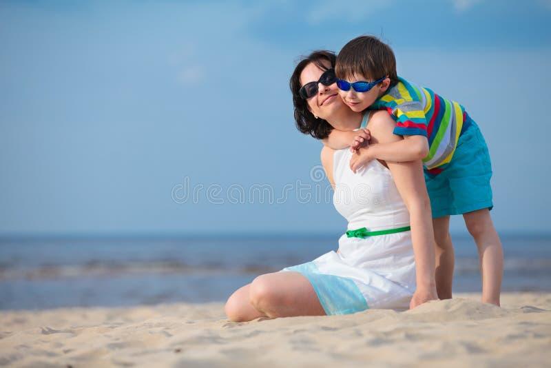Mutter und Sohn, die Zeit am tropischen Strand genießen lizenzfreie stockbilder