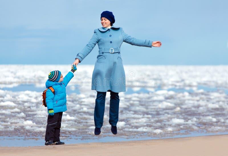 Mutter und Sohn, die Zeit am Winterstrand genießen stockfotos
