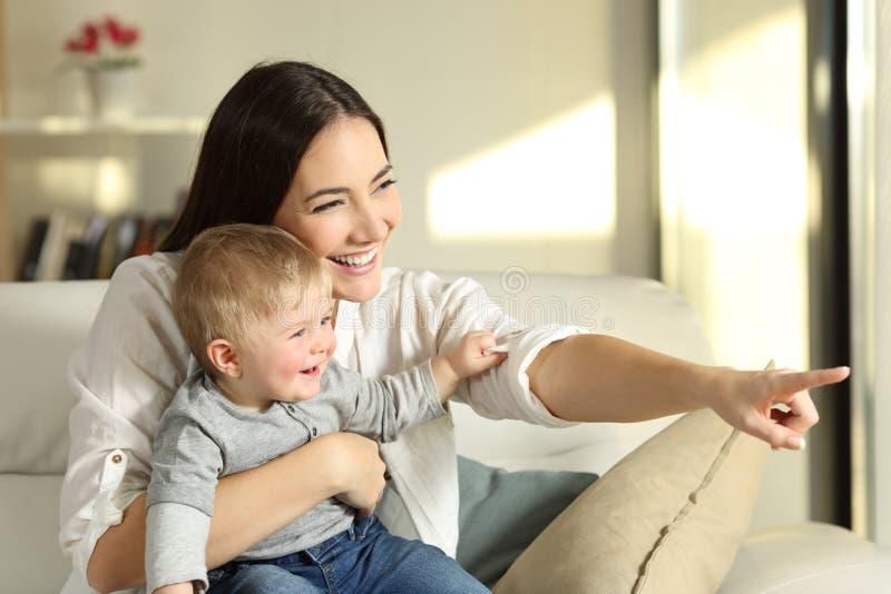Mutter und Sohn, die zu Hause durch ein Fenster schauen stockfoto