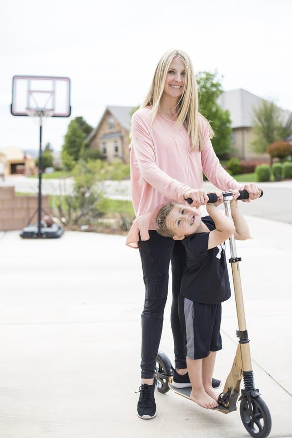 Mutter und Sohn, die zusammen auf einem Roller in der Fahrstraße spielen stockbilder