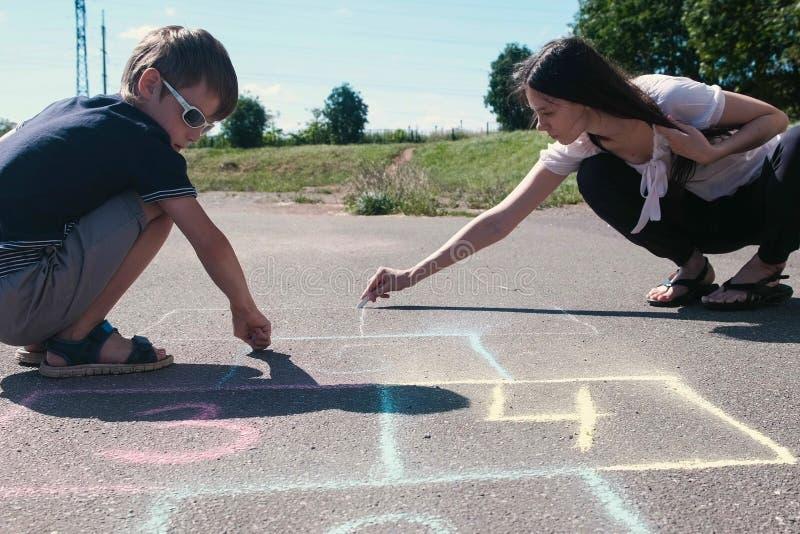 Mutter und Sohn, die zusammen Hopse auf der Pflasterung zeichnen lizenzfreie stockbilder