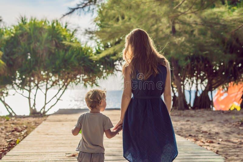 Mutter und Sohn gehen zum Seestrand Erholungsortferien auf tropischem Strand Pfad zum auf den Strand zu setzen lizenzfreie stockfotografie