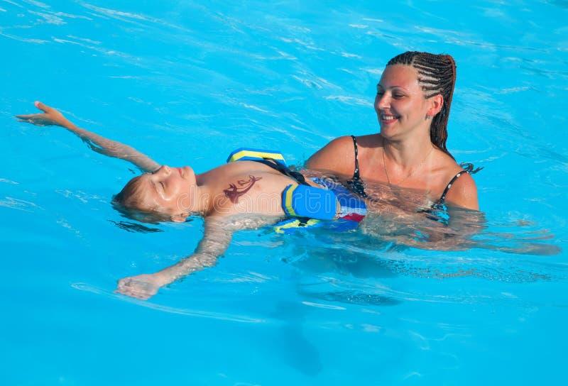 Mutter und Sohn haben Spaßschwimmen lizenzfreies stockbild