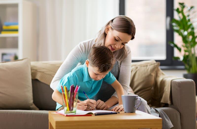 Mutter und Sohn mit Arbeitsbuch zu Hause lizenzfreies stockbild