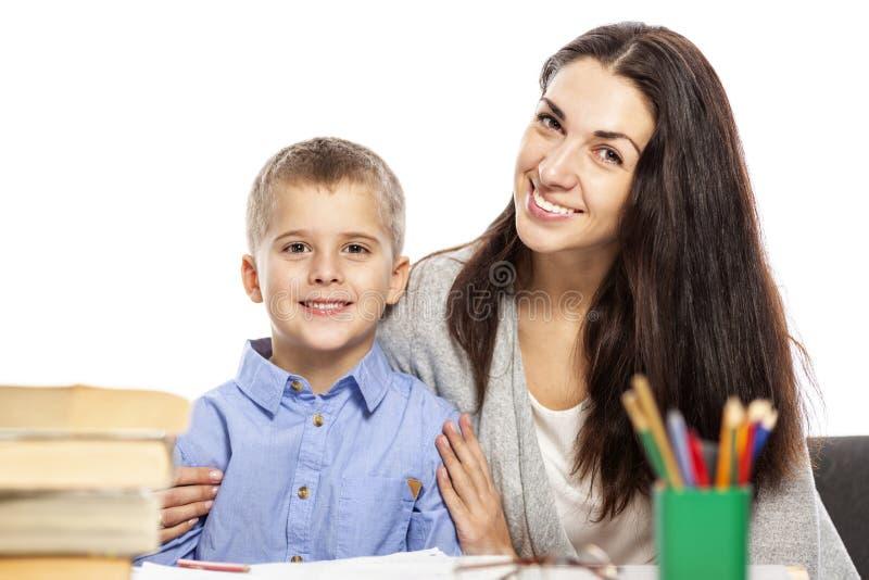 Mutter und Sohn sind lächelnd und beim Handeln ihrer Hausarbeit umarmend Liebe und Weichheit Wei?er Hintergrund stockfotografie