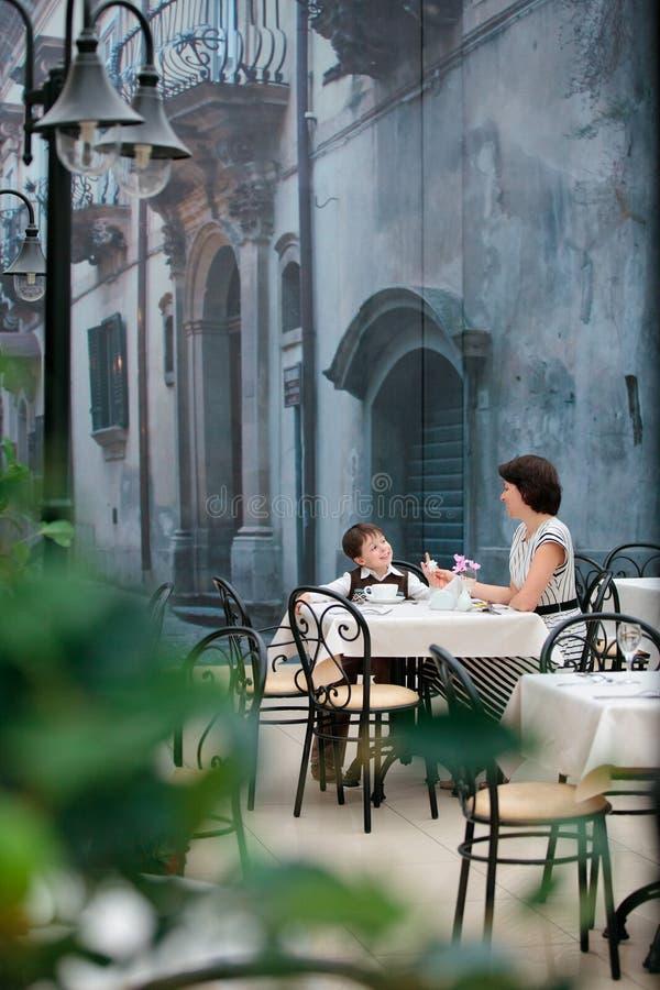 Mutter und Sohn, welche die Mahlzeit sitzt am Kaffee genießt lizenzfreie stockfotografie