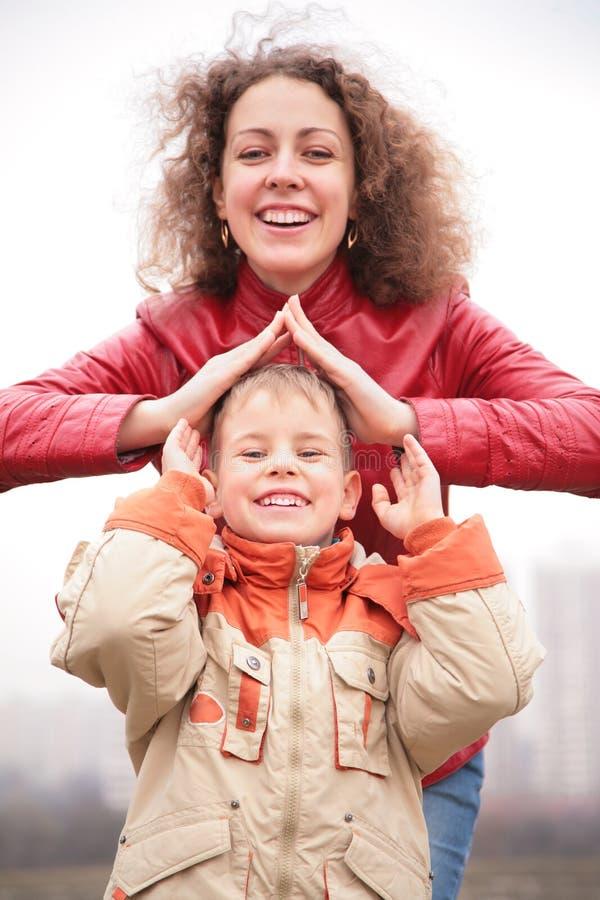 Mutter und Sohn zeigen Haus von den Händen stockfotos