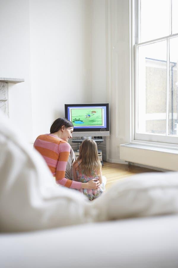 Mutter-und Tochter-aufpassende Karikaturen in Fernsehen stock abbildung