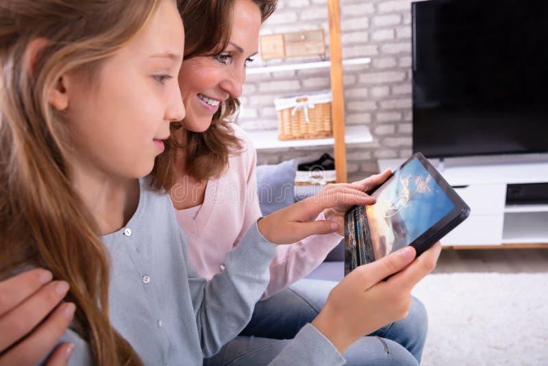 Mutter-und Tochter-aufpassendes Video auf Digital-Tablet lizenzfreie stockfotos