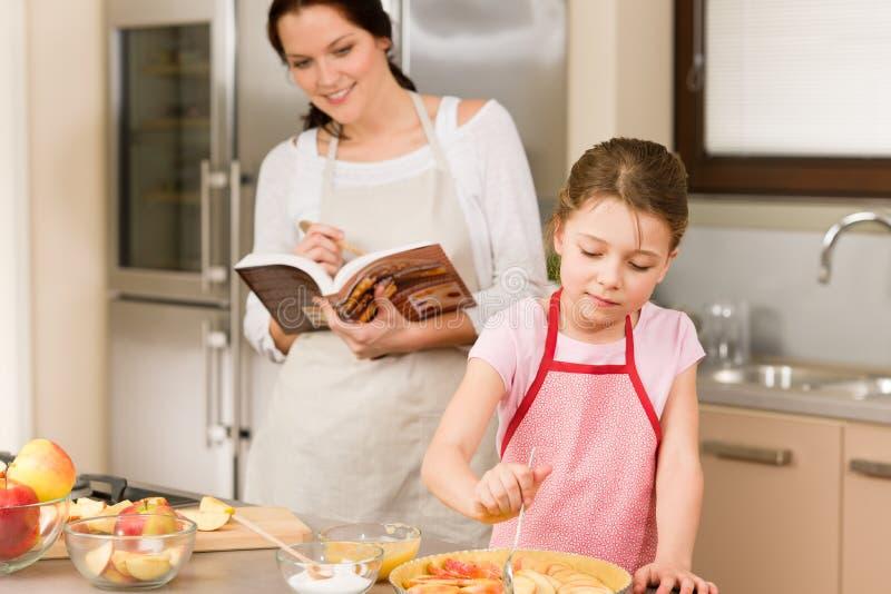 Mutter und Tochter bilden Apfelkuchenrezept stockbild