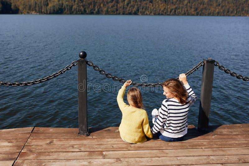Mutter und Tochter der hinteren Ansicht, die am warmen Herbsttag des Piers sitzen stockbild